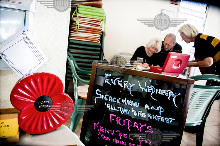A woman buying a raffle ticket, the menu and a giant plastic poppy from the previous year's appeal at the The English Speaking Club El Campello. Spain is home to more British ex-pats than anywhere else in the world, mostly concentrated in its Mediterranean regions and there are numerous clubs and organisations catering to this population. The English Speaking Club El Campello, whose president is former RAF and the vice-president a former policeman, organises raffles, dances, trips and games etc and has over 400 members.