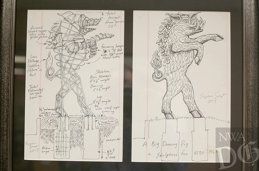 NWA Democrat-Gazette/DAVID GOTTSCHALK Drawings by artist Eugene Sargent of a 25 foot tall boar are framed Wednesday, June 6, 2018, inside the office of Cliff Slinkard with Hogeye Inc. Sargent was commissioned by Slinkard to design and build the boar that will be installed Sunday, June 10, 2018 and a five foot tall base at the company office at 4148 West Matin Luther King Jr. Boulevard in Fayetteville.