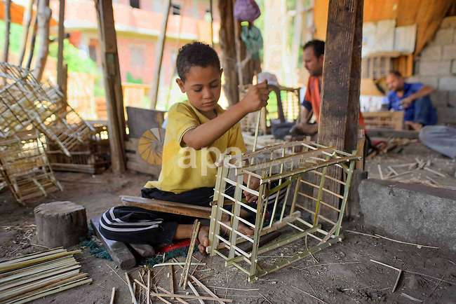 An Egyptian boy weaves straw-traditional products, at their workshop, in Cairo, Egypt, on September 7, 2016. Photo by Amr Sayed