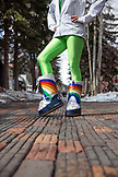USA, Colorado, Aspen, a young woman in green leggings stands in her moonboots in the square in downtown Aspen