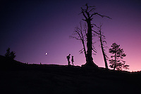 A French couple at the Sentinel Dome in Yosemite National Park photograph each other at sunset.