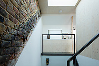 A Victorian home has been given a modernist aesthetic. The first floor landing was replaced with high-strength glass whilst leaving the original brickwork exposed lends a rustic touch. The other walls are clad in birch plywood.