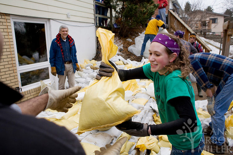 "Volunteer and Concordia College junior Annie Erickson helps sandbag the home of Richard Pemble, left, on Tuesday morning (March 15, 2010) in a neighborhood just north of Interstate 94 in Moorhead, Minn. ""They're doing a fantastic job,"" Pemble said of the volunteers who hope to protect the property from a rising Red River to 40 feet. Pemble has lived in his home for 25 years and this is the sixth time a sandbag dike has been built on his property."
