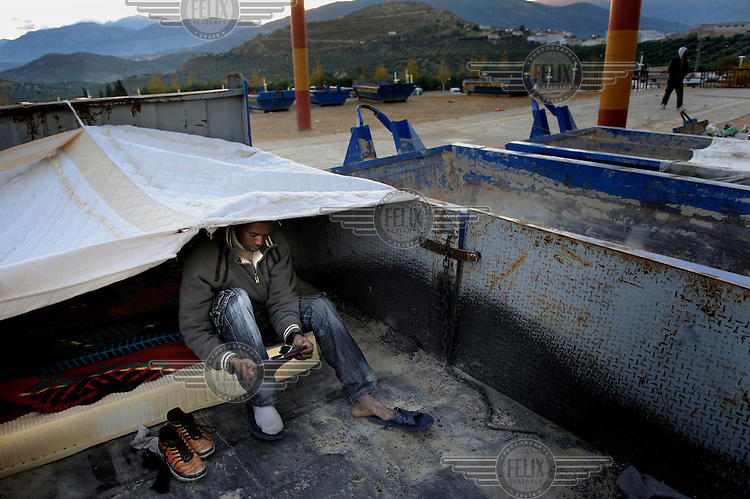 An illegal migrant worker gets dressed after sleeping the night in a container. Many of migrants come to the region to pick olives but this year there is competition for the work. The economic collapse means that work once shunned by the indigenous population is now sought after by unemployed Spaniards.
