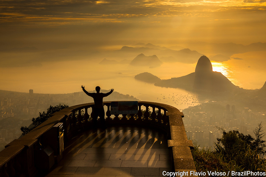 Sunrise in Rio de Janeiro seen from the Christ the Redeemer statue point of view, with Sugar Loaf Mountain and Guanabara Bay entrance in background.