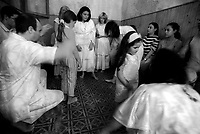 """Mae Susana and her assistants perform a """"santiguado"""", the cleaning of the aura of a person from negative energies, during an Umbanda spiritual session in Montevideo Uruguay. Followers of Umbanda have increased dramatically in past years in Uruguay, where more than 200 existing temples are attended mostly by members of the middle lower class looking for hope in escaping poverty. For the last two years Uruguay is immersed in a deep socioeconomic crisis, unemployment had reach unrecognizable levels, leaving vast sectors of the population in poverty and disillusion Photo by Quique Kierszenbaum."""