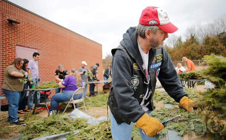 NWA Democrat-Gazette/DAVID GOTTSCHALK  Wes Offenbacker, a volunteer with with Bo's Blessings from Springdale, breaks down wreaths Friday, February 19, 2016, as she participates in the fourth annual Wreath Recycling Event at the National Guard Armory in Fayetteville. More than 9,000 wreaths collected from the Fayetteville National Cemetery are being broken down for recycling purposes and a bonfire memorial service. All money raised from the event will be donated to the Regional National Cemetery Improvement Corporation for land purchases for the cemetery. Bo's Blessings is a non-profit organization honoring Bo Swearingen, an Army veteran, who died in April of 2010.