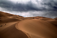 Storm clouds pass over three hikers on Eureka Dunes at Death Valley National Park, California