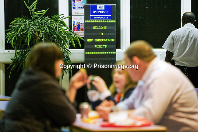 A Prisoner sits with his partner and their daughter, in the visitors centre at HMP Wandsworth in South West London. Families can visit prisoners every Monday afternoon.
