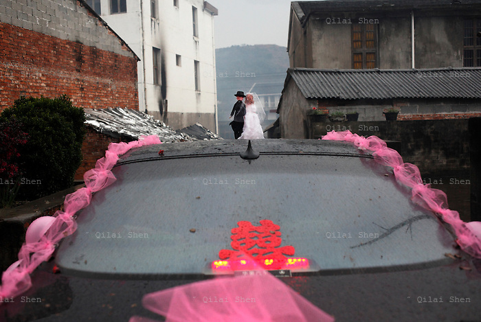 A wedding in Wenzhou, China on 12 March 2009. Wenzhou is known for its hard working private entrepreneurs and the resulting wealth. In this region marriage such as this one is a particular important occasion not only for the newly weds but also for the groom's family to show its wealth and social standing. Here the large Mercedes sedan that the groom uses can hardly fit in the narrow lane that leads up to the bride's village home.