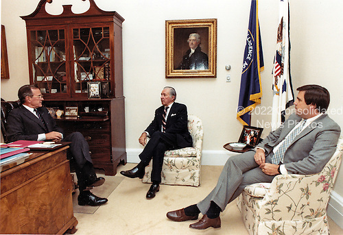 United States Vice President George H.W. Bush, left, discusses US President Ronald Reagan's schedule with Donald Regan, Chief of Staff to the President, center, and Craig Fuller, Chief of Staff to the Vice President.  The three men met shortly before noon on July 15, 1985 in the Vice President's West Wing office.  Vice President Bush cancelled a trip to Missouri and Ohio in order to be in Washington this week for the conduct of official business.<br /> Mandatory Credit: David Valdez / White House via CNP