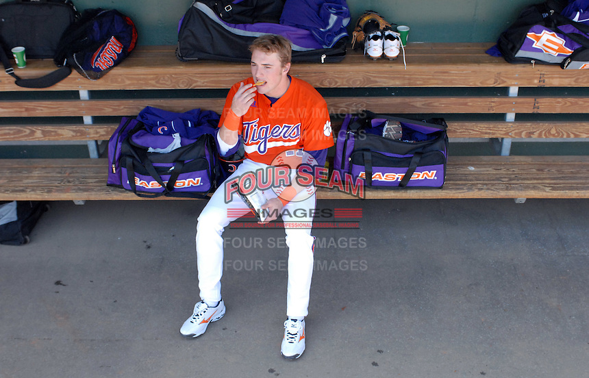 Outfielder Kyle Parker (11) of the Clemson Tigers snacks in the dugout prior to a game against the Michigan State Spartans Saturday, Feb. 20, 2010, at Fluor Field at the West End in Greenville, S.C. Parker is ranked No. 73 on Baseball America's list of top 100 college prospects. Photo by: Tom Priddy/Four Seam Images