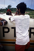 "Amazon, Brazil. Young Kayapo; ""I gave to save the rainforests"" T-shirt; aircraft in Capoto village, Megranoti Reserve."