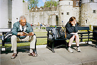 An old man reading a book seatting on park bench near to a young lady