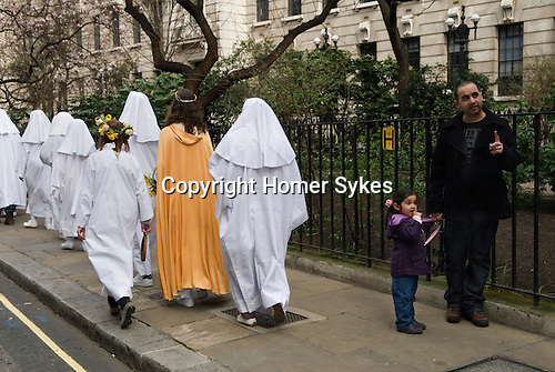 Druids perform a Spring Equinox ceremony at Tower Hill London. UK Annually March. They are walking back to their meeting place to disrobe.