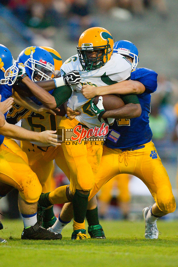 Kenny Purvis (6) of the Central Cabarrus Vikings is wrapped up by several Mount Pleasant Tigers defenders at Mount Pleasant High School on August 23, 2013 in Mount Pleasant, North Carolina.  The Vikings defeated the Tigers 13-0.  (Brian Westerholt/Sports On Film)