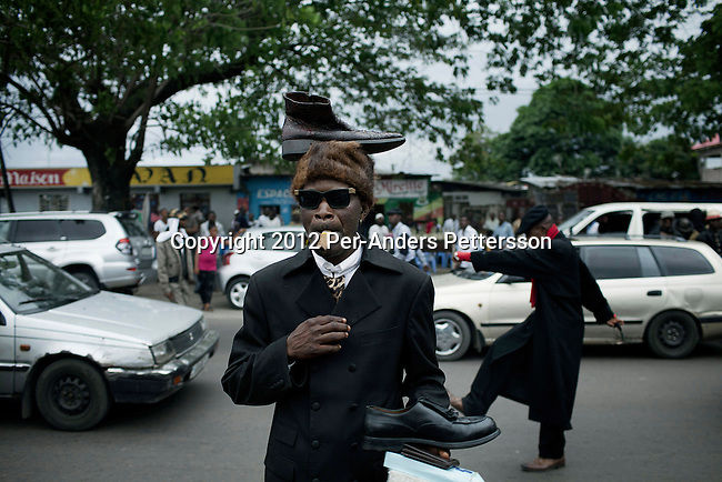 "KINSHASA, DEMOCRATIC REPUBLIC OF CONGO - FEBRUARY 10: A senior Sapeur shows his designer label clothes and shoes on a busy street while paying his respect to Stervos Nyarcos, the founder of the kitendi religion, which means clothing in local language Lingala. Nyarcos was known as the leader of the Sape movement, at Gombe cemetery on February 10, 2012 in Kinshasa, DRC. The word Sapeur comes from SAPE, a French acronym for Société des Ambianceurs et Persons Élégants or Society of Revellers and Elegant People and it also means, to dress with elegance and style"". Most of the young Sapeurs are unemployed, poor and live in harsh conditions in Kinshasa,  a city of about 10 million people. For many of them being a Sapeur means they can escape their daily struggles and dress like fashionable Europeans. Many hustle to build up their expensive collections. Most Sapeurs could never afford to visit Paris, and usually relatives send or bring clothes back to Kinshasa. (Photo by Per-Anders Pettersson)"