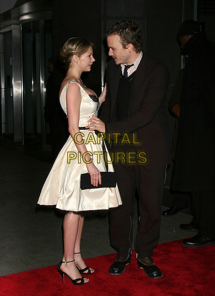 "MICHELLE WILLIAMS & HEATH LEDGER.""Brokeback Mountain"" New York Premiere at Loews Lincoln Square, New York City..December 6th, 2005.Ref: IW.full length white dress black clutch purse profile celebrity couple boyfriend girlfriend black suit.www.capitalpictures.com.sales@capitalpictures.com.©Capital Pictures"