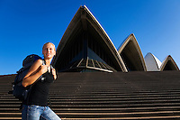 A young backpacker looks out from the steps of the Sydney Opera House.  Sydney, New South Wales, AUSTRALIA.