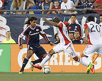 New England Revolution midfielder Juan Carlos Toja (7) dribbles as Toronto FC midfielder Reggie Lambe (19) defends. In a Major League Soccer (MLS) match, Toronto FC (white/red) defeated the New England Revolution (blue), 1-0, at Gillette Stadium on August 4, 2013.
