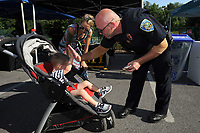 NWA Democrat-Gazette/ANDY SHUPE<br /> Dallas Brashears (right) of the Fayetteville Police Department hands out a sticker Tuesday, Aug. 6, 2019, to Axel Rogers, 2, of Fayetteville as his mother, Megan Scheerschmidt watches during the National Night Out event at Wilson Park. Night Out events are organized to foster stronger relationships between police and community members and to build bonds among neighbors through similar events across the country on the first Tuesday of August.