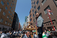 A mikoshi supporter prepares to knock two pieces of wood together to signal the crowd to carry a mikoshi, or portable shrine, in the bi-annual Kanda matsuri (festival). Chiyoda Ward, Tokyo, Japan Sunday May 10th 2015. Over 200 mikoshi are carried through the streets of central Tokyo every 2 years in this spring festival