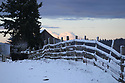 Split rail wooden fence and old barn with snow