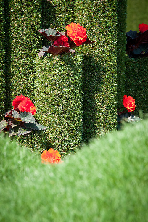 Diamonds and Rust show garden, designed by Tony Smith, Hampton Court Flower Show 2011. Featuring artificial grass columns and Begonia 'Nonstop Mocca Deep Orange'.