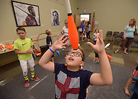 NWA Democrat-Gazette/BEN GOFF @NWABENGOFF<br /> Pablo Fajardo, 11, of Bentonville tries to balance a juggling pin on his head on Thursday June 9, 2016 after watching a performance by Ellen Winters and Galen Harp of Institute of Jugglology from Fayetteville at the Bentonville Public Library.