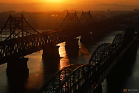 The sun rises behind the Friendship and the Broken bridges over the Yalu River connecting the North Korean town of Sinuiju and Dandong in China's Liaoning Province, November 19, 2017. REUTERS/Damir Sagolj