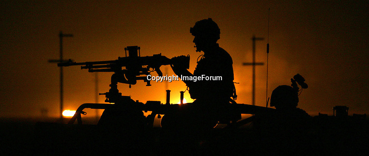Members of the Royal Air Force Regiment 1st Squadron pass an oil and gas seperation terminal  while carrying out a night patrol on the perimeter of Basra Airport Base in southern Iraq, in the early hours of 12 October 2005, ahead of the constitutional referendum on 15 October. The RAF Regiment is tasked with protecting airbases and other RAF assets around the world. AFP PHOTO / JOHN D MCHUGH