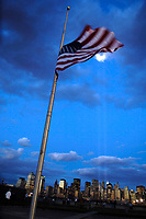 Sept 11, 2006 - File Photo - An American flag waves in the wind with the ?Tribute in Light? memorial in the background at Liberty State Park, New Jersey on September 11, 2006. The ?Tribute in Light? memorial is in remembrance of the events of September 11, 2001, in honor of the citizens who lost their lives in the World Trade Center attacks. The two towers of light are composed of two banks of high wattage spotlights that point straight up from a lot next to Ground Zero. The ?Tribute in Light? memorial was first held in March 2002. This photo was taken from Liberty State Park, New Jersey on September<br /> 11, 2006, the five year anniversary of 9/11. USAF photo by Denise Gould.