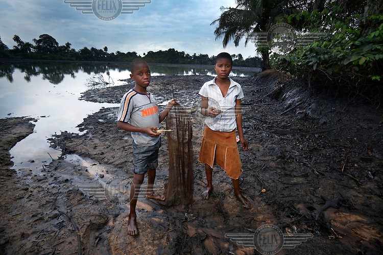Victor and Queen Dooh, at one of their family's fish ponds that was completely destroyed by an oil spill from a Shell pipeline. The family launched proceedings against the oil giant in 2009.