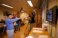 Journalist Htet Aung Kyan watching events in Burma while being filmed by crew from Swiss TV channel TSR. Democratic Voice of Burma is radio and TV station run by exiled Burmese. Opposing the government, the DVB has been transmitting, from the Norwegian capitol Oslo, into Burma since 1992.