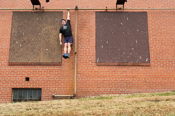 December 22, 2014. Lexington, North Carolina.<br />  Mayor Newell Clark hangs from the wall of the abandoned Lexington Furniture factory as part of his workout routine with local citizens.<br />   Newell Clark, the 43 year old mayor of Lexington, NC, leads a group of friends and colleagues on a 4 times a week exercise routine around downtown. The group uses existing infrastructure, such as an abandoned furniture factory, loading docks, stairs, and handrails to get fit and increase awareness of healthy lifestyles in a town more known for BBQ.<br /> Jeremy M. Lange for the Wall Street Journal<br /> Workout_Clark