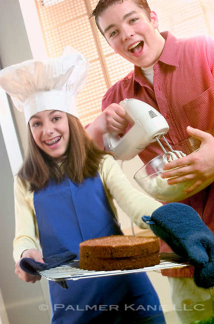 Two teens having fun while making a cake and whipping cream for frosting