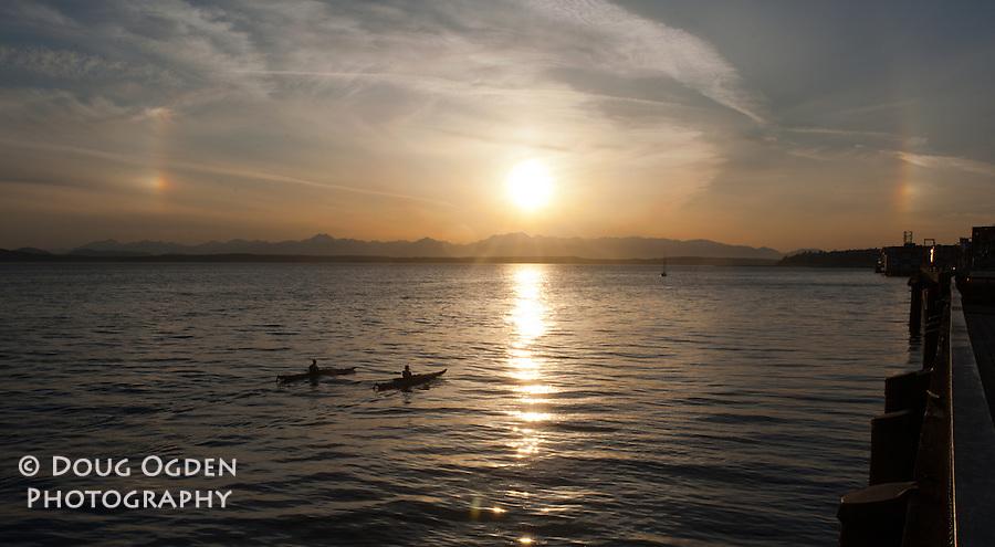 Kayakers on Elliot Bay during Sun Dog sunset, Seattle