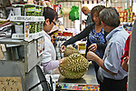 People buying Asian durian fruit in grocery store.