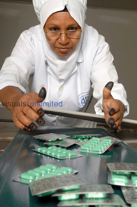 A female worker collecting packages of drugs off a conveyor belt in a pharmaceutical factory..