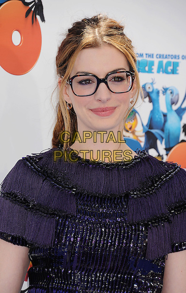 """ANNE HATHAWAY.The Los Angeles Premiere of """"Rio"""" at Grauman's Chinese Theatre in Hollywood, California, USA.April 10th, 2011.headshot portrait glasses geek tortoiseshell purple hair up tassels tassel fringed beaded.CAP/ROT/TM.©Tony Michaels/Roth Stock/Capital Pictures"""