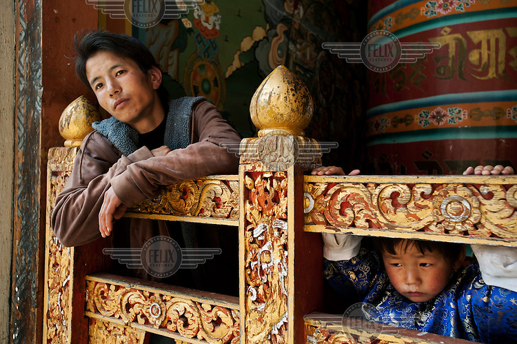 A man and boy stand next to a huge prayer wheel at the Tango Dzong Monastery.
