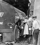 A large tank truck with fresh drinking water draws a crowd waiting with pitchers, milk cans and other containers.