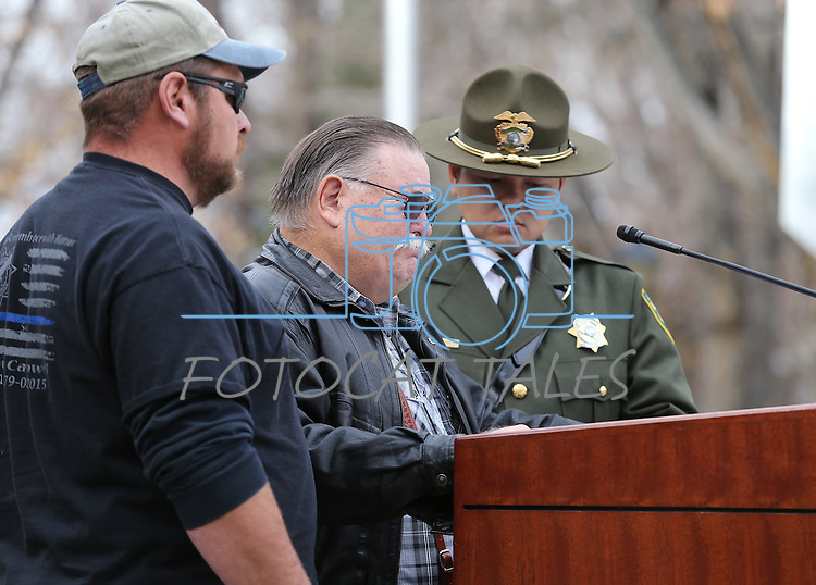 Corey Howell, left, and Dep. Michael Huynh, right, comfort Kevin Howell, center, during a ceremony to unveil a freeway sign dedicating I-580 in honor of Howell's son Carson City Sheriff's Deputy Carl Howell at the Nevada Law Enforcement Officers Memorial in Carson City, Nev., on Tuesday, Dec. 8, 2015. Dep. Howell was killed in the line of duty on Aug. 15, 2015. <br /> Photo by Cathleen Allison/Nevada Photo Source