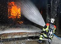 Den Bosch. Open dag van de Brandweer. Brandweerman blust een brand in een container