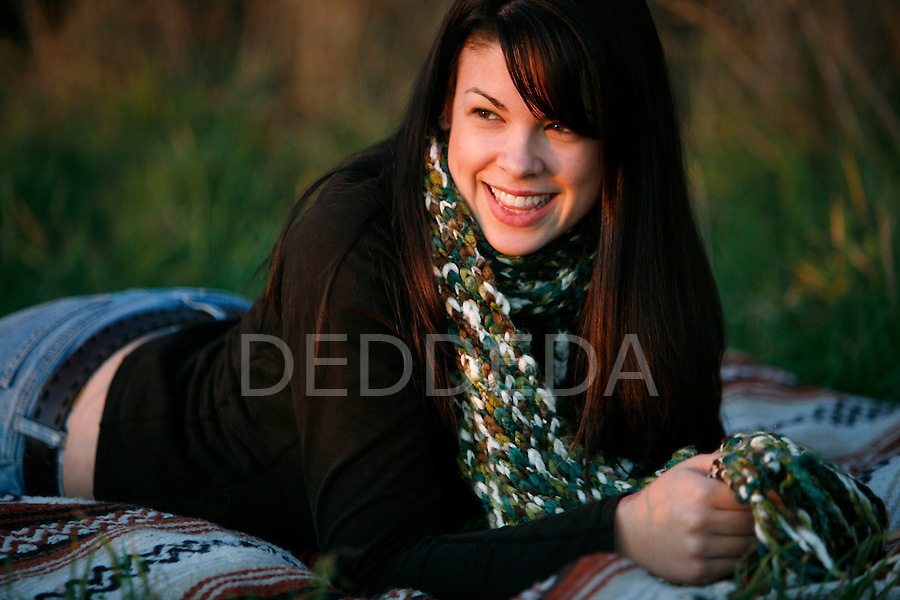 A young woman lies on a blanket on the grass in Victoria, British Columbia, Canada on Vancouver Island..