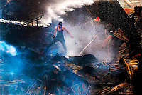 Bangladeshi firefighters and residents try to control a fire at the Begunbari slum in Dhaka, Bangladesh.
