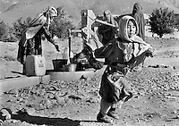 Recently returned from growing up as a refugee in Iran, a young Hazara girl runs past a water pump in Ghazni, Aghanistan on June 19, 2002. Many Afghan children are forced by poverty to work rather than go to school. More than six million people fled Afghanistan during the years of conflict following the Soviet invasion in 1979.