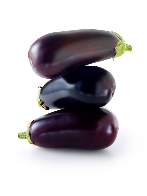 Whole fresh aubergines against a while background