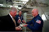 United States President Bill Clinton prepares to use a fork to sample some space food while visiting NASA's Johnson Space Center (JSC) on April 14, 1998. Holding the food packet is U.S. Senator John H. Glenn Jr. (Democrat of Ohio), currently in training at JSC as a payload specialist for a flight scheduled later this year aboard the Space Shuttle Discovery. Looking on is astronaut Curtis L. Brown Jr., STS-95 commander. The picture was taken in the full fuselage trainer (FFT). .Credit: Joe McNally, National Geographic for NASA via CNP