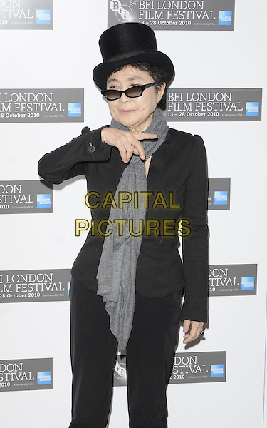 "YOKO ONO .Attending the ""LennoNYC"" premiere  during the 54th BRI London Film Festival, Vue West End, Leicester Square, London, England, UK, .October 29th 2010..half length lennon nyc black top hat jacket trousers suit grey gray scarf sunglasses hand finger pointing gesture .CAP/CAN.©Can Nguyen/Capital Pictures."
